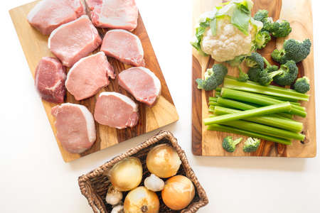 Boneless raw pork loin chops, fresh cauliflower, broccoli, celery, onion and garlic. Meat and vegetables close up on wooden cutting boards on white background