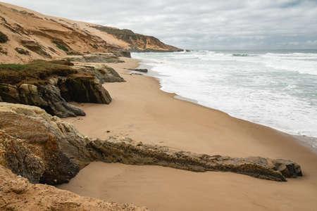 Scenic seascape. Rocky cliffs and Pacific Ocean, dramatic cloudy sky background. California Coastline