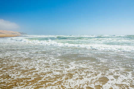 Seascape background. Empy sand beach, ocean waves, and clear blue sky on background
