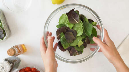 Lettuce salad in a glass bowl close up on kitchen table, view from above