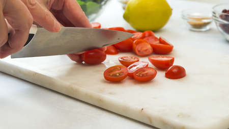 Cherry tomatoes close up on cutting board. Cheff cuts tomatoes. Vegetable salad recipe