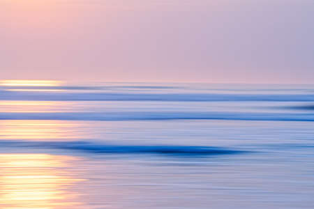 Abstract seascape with blur panning motion. Sunrise or sunset over sea, beautiful soft light blue and pink colors