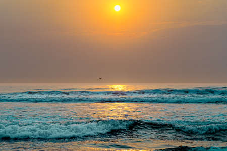 Scenic seascape, sunset over the ocean. Tranquil scene, beautiful sun reflection and stormy ocean waves