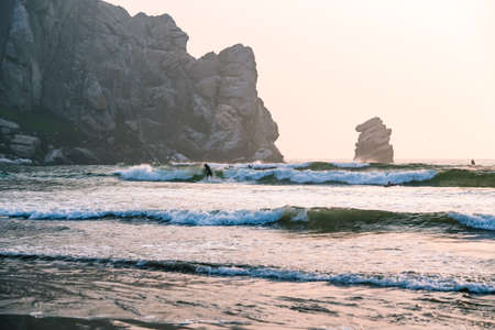 Morro Bay State Park, California/USA  - September 13, 2020.  Surfing at Marro Bay at sunset, California Coastline. Stormy ocean, and famous Marro Rock at sunset