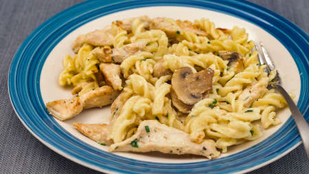 Pasta with mushrooms, chicken meat and Alfredo sauce close up on a plate