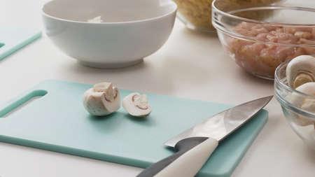Fresh raw  chopped organic white mushrooms close up on cutting board on white background