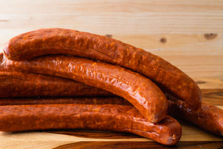 Smoked pork sausages close up on wooden background