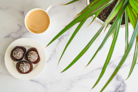 Coffee time. Cup of coffee, chocolate candy close up on marble table, flat lay with copy space
