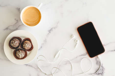 Coffee time. Cup of coffee, chocolate candy, cellphone, headphone close up on marble background, flat lay, copy space. Stock Photo