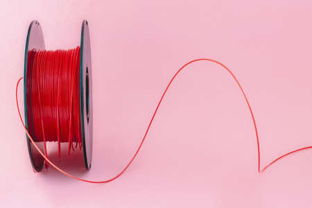 3D Printer Plastic Filament. Spool of red thermoplastic wire for 3D printing close up isolated on pink background Stock Photo