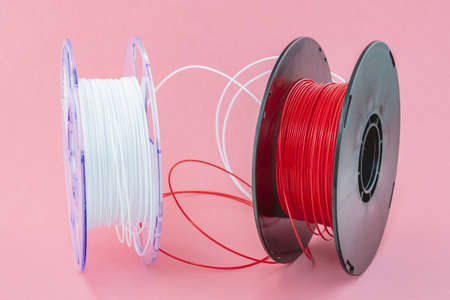 3D Printer Plastic Filament. Spool of white and red thermoplastic wire for 3D printing close up isolated on pink background Stock Photo