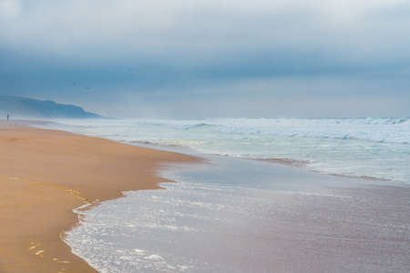 Abstract dreamlike seascape in soft blue color. Stormy ocean, sandy beach, and cloudy sky in an overcast day Stock Photo