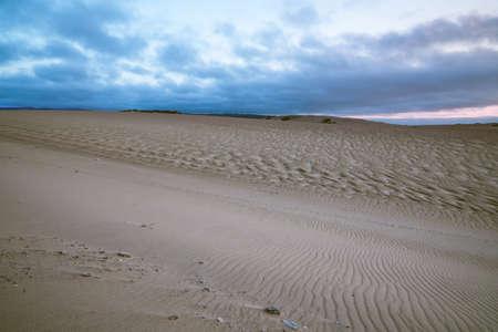 Sand dunes, blue hour. Horizon over land, cloudy sky background Stock Photo