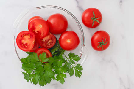 Fresh red organic tomatoes and fresh parsley close up on a glass plate on marble background directly from above Stock Photo