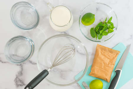 Lemon pudding or lemon curd  served with mint leaves and sliced lemon recipe. Ingredients close up on marble background directly from above. Sweet cream, delicious dessert preparation process