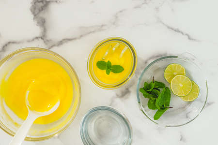 Lemon pudding with fresh mint leaves and sliced lemon recipe. Ingredients close up on marble background with copy space Stock Photo