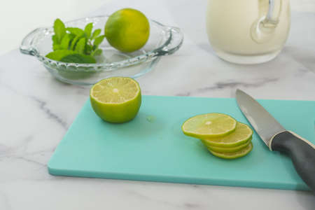 Lemon slices close up on cutting board on marble kitchen table Stock Photo