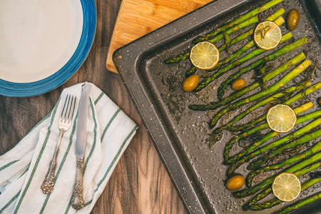 Green asparagus baked with olives, rosemary, mint leaves, sliced lemon, and seasoning close up on wooden kitchen table