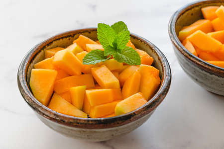 Cantaloupe melon bite-sized cubes served with mint leaves close up in a bowls on light marble background. Fruit salad, dessert