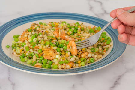Blend of couscous, orzo, garbanzo beans, red quinoa cooked with shrimps and served with green peas and green onion close up on a plate on white background