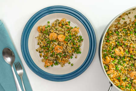 Blend of couscous, orzo, garbanzo beans, red quinoa cooked with shrimps and served with green peas close up on a plate on white background directly from above