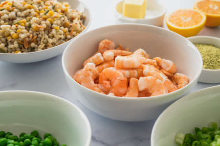 Blend of couscous, orzo, garbanzo beans, and red quinoa, shrimps, green peas, and chopped green onion in bowls close up on marble background