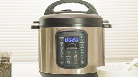 Modern electric multi cooker close up on kitchen table. Up to 20 minutes cooking time selection Stock Photo