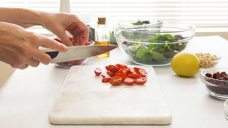 Chef cuts cherry tomatoes. Lettuce salad with tomatoes and honey mustard salad dressing recipe.