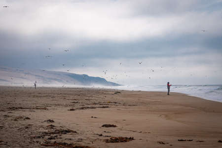 Foggy day on the beach. Silhouette of fisherman, flock of birds and dramatic cloudy sky on background Stock Photo