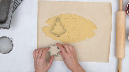 Christmas shortbread cookies with raspberry jam recipe. Chef using cookie cutters to stamp Christmas cookies, pine tree cutter and star cutter