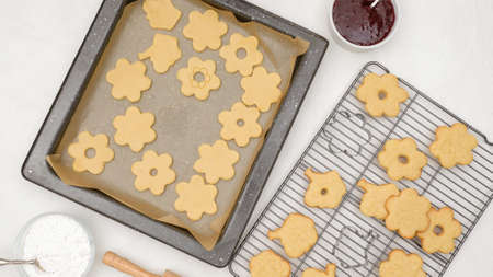 Shortbread cookies with raspberry jam recipe. Step by step baking process, flat lay. Cookies close up on baking pan and cooling rack