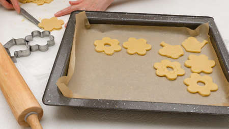 Shortbread cookies with raspberry jam recipe. Step by step baking process. Woman placing cookies on a prepared baking pan