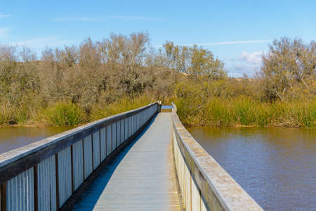 Wooden boardwalk through the lake. Quiet blue water with sun reflections, and beautiful cloudy sky background. Oso Flaco Lake, Oceano, California Zdjęcie Seryjne