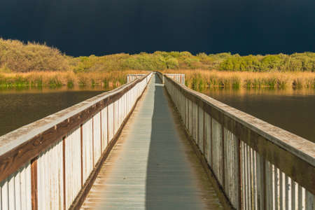 Lake and long wooden boardwalk through the lake with dark blue sky on background, few minutes before the storm. Oso Flaco Lake Natural Area in Oceano, California Zdjęcie Seryjne