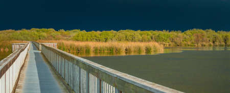 Panoramic landscape of lake and long wooden boardwalk through the lake with dark blue sky on background, few minutes before the storm. Oso Flaco Lake Natural Area in Oceano, California Zdjęcie Seryjne