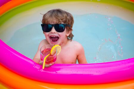 Happiness. Summer rest. The child screams with pleasure. Laugh and smile. The boy in the pool.