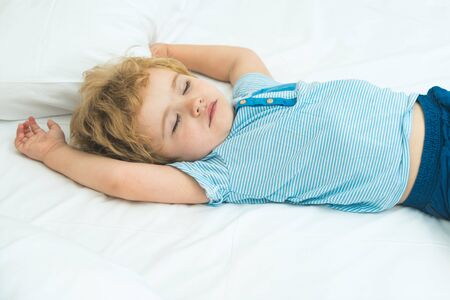 Adorable little blond kid boy in clothes sleeping and dreaming in his white bed. Healthy child with soft bad, peaceful sleep at home.