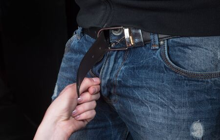 Girl undresses the man. A womans hand removes a leather belt with mens jeans. Sexy evening before sex, couple at an intimate moment. Husband and wife, boyfriend and girlfriend. Erection and arousal.