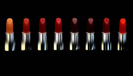 Red lipstick. Cosmetics on black background isolated. Lipsticks on black. High quality lipstick. Daily make up. Cosmetics artistry. Lipstick professional make up. Makeup products. Lip care concept.