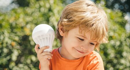 Handsome boy with a light bulb. An elaborate explorer. The lessons of physics. Little scientist. A smart boy teaches how a light bulb works. Cute child with idea icon.
