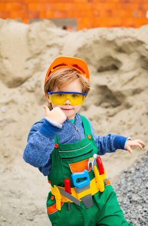 Builder thumb up. The boy is dressed as a builder. Future profession. Career guidance. Happy successful builder. Career. Business in the construction industry. The property. Child game. Archivio Fotografico - 129176521