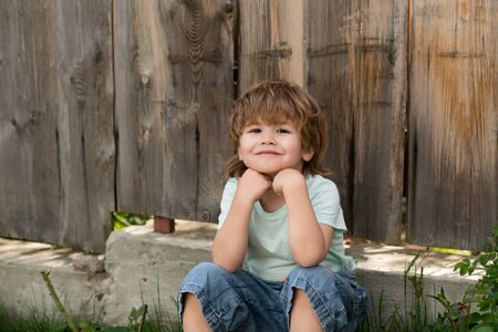 Happy boy. A child with a smile. Kid sits near a wooden fence. Happy summer. August or September. Stok Fotoğraf