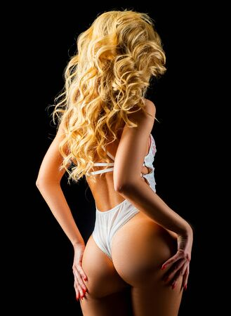 Sexy woman body part in white panties. Photo of beautiful female back in white lingerie. Curly blonde woman, back view.