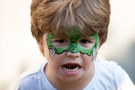 Dragon body art. Child with a mask on his face. Carnival. Favorite hero for a childrens party. Green face and fangs. A game. Fun for kids. Childrens theater. Kindergarten and party for preschoolers. Zdjęcie Seryjne
