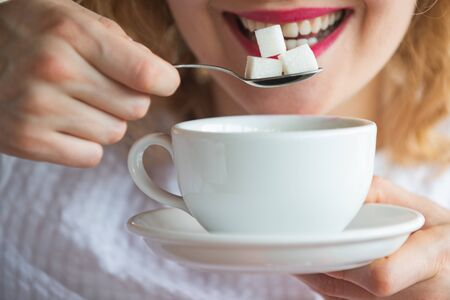 Sugar. Sweet. A woman holds sugar cubes on a spoon. Beautiful female mouth and calories concept. Coffee and tea. Sweet drink. Teeth, Health and Junk Food.
