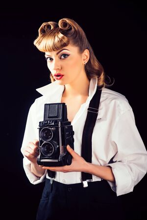Retro vintage concept. Beautiful woman holding a camera. Old style. The best moments of life on film. Banque d'images - 131765661