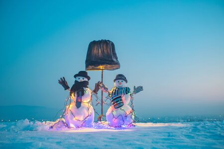 Two snowmen under a lamp. Couple the background of blue sky. Good winter installation for holidays. Snowmen in the snow, clear winter night.