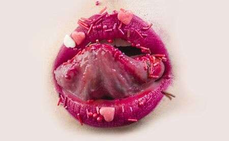 Tongue in open female mouth. Sweet lips with sweets. Woman licks pink hearts. Seductive sensual mouth of young girl with pink lipstick, sweet cosmetics concept. Delicious dessert and food.