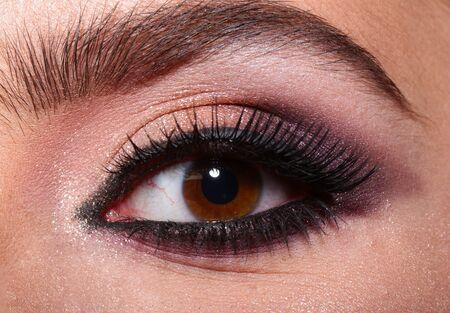 Woman eye with beautiful makeup. Beautiful female eye with extreme long eyelashes and smoky makeup. Perfect eyebrows and long lashes. Cosmetics and make-up. Closeup macro shot of fashion eyes visage.