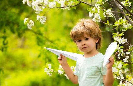 Aircraft. Cheap flights. Traveling with children. The boy holds paper airplanes. Low cost flights. Vacations and vacations. A child in the garden is playing. Avia.